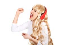 Gelukkige vrouw die en aan de muziek zingen luisteren Royalty-vrije Stock Foto