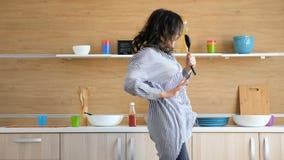Gelukkige vrouw die en in de keuken dansen zingen stock videobeelden