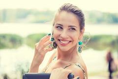 Gelukkige vrouw die en in de straat glimlachen lopen die op een smartphone spreken stock fotografie