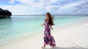 Gelukkige vrouw die, en havng pret op oceaanstrand van de Maldiven glimlachen lopen stock videobeelden
