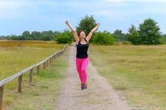 Gelukkige vrouw die en na het uitwerken van jogging toejuichen vieren stock afbeelding