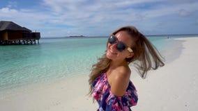 Gelukkige vrouw die, en op oceaanstrand van de Maldiven glimlachen wervelen lopen stock footage