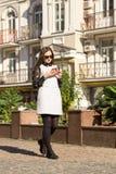 Gelukkige vrouw die en slimme telefoon op stadsstraat lopen met behulp van Stock Foto's