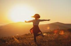Gelukkige vrouw die en van het leven springen genieten bij zonsondergang in bergen Stock Afbeeldingen