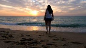 Gelukkige vrouw die en van het water op het strand spelen lopen stock videobeelden