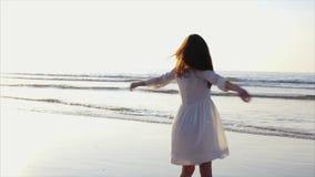Gelukkige vrouw die en zich op strand omdraaien tollen stock footage