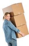 Gelukkige Vrouw die Gestapelde Kartondozen dragen Stock Foto's