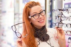Gelukkige vrouw die glazen kiezen bij opticaopslag stock fotografie