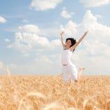 Gelukkige vrouw die in tarwe springen Stock Foto's