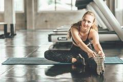 Gelukkige vrouw die haar been uitrekken bij gymnastiek stock foto