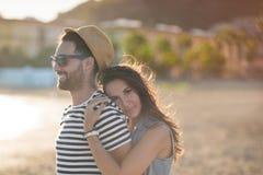 Gelukkige vrouw die haar vriend omhelzen bij kust het glimlachen royalty-vrije stock foto's