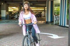 Gelukkige vrouw die helm berijdende fiets in de zomer dragen stock afbeeldingen