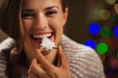 Gelukkige vrouw die het koekje van Kerstmis eet stock foto's