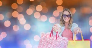 Gelukkige vrouw die het winkelen zakken over bokeh tonen Stock Afbeeldingen