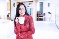 Gelukkige vrouw die hete koffie thuis houdt stock foto's