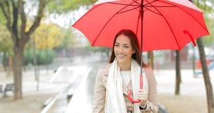 Gelukkige vrouw die houdend een paraplu onder de regen lopen stock videobeelden