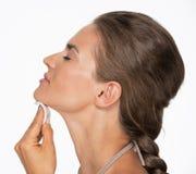 Gelukkige vrouw die katoenen stootkussen gebruiken om make-up te verwijderen Royalty-vrije Stock Foto's