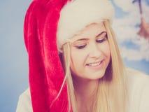 Gelukkige vrouw die in Kerstmanhoed over Kerstmis denken Royalty-vrije Stock Foto's