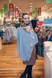 Gelukkige vrouw die in kledingsopslag winkelen Stock Fotografie