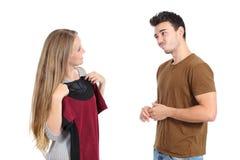 Gelukkige vrouw die kleren proberen die met haar vriend winkelen stock afbeeldingen