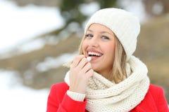 Gelukkige vrouw die lippenpommade in openlucht in de winter toepassen stock fotografie