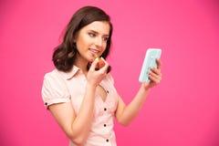 Gelukkige vrouw die lippenstift op lippen zetten Royalty-vrije Stock Afbeeldingen