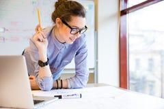 Gelukkige vrouw die met blauwdruk dichtbij het venster in bureau werken Stock Foto's