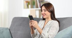 Gelukkige vrouw die met een smartphone thuis babbelen