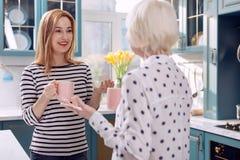 Gelukkige vrouw die met haar hogere moeder in keuken babbelen royalty-vrije stock afbeeldingen