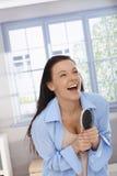 Gelukkige vrouw die met in hand haarborstel lacht Stock Fotografie