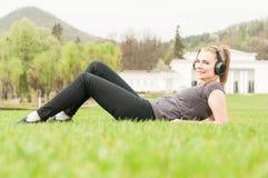 Gelukkige vrouw die met hoofdtelefoons aan muziek buiten luisteren Stock Afbeeldingen