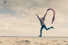 Gelukkige vrouw die met sjaal op strand springen royalty-vrije stock afbeelding