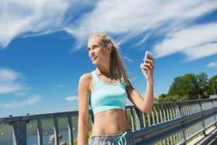 Gelukkige vrouw die met smartphone in openlucht uitoefenen Royalty-vrije Stock Foto