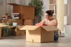 Gelukkige vrouw die naar huis unboxing bezittingen in de nacht bewegen royalty-vrije stock afbeelding