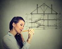 Gelukkige vrouw die nieuw huisplan met potlood trekken stock afbeeldingen