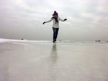Gelukkige vrouw die op bevroren overzees lopen een koude dag stock afbeelding