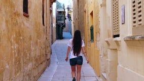Gelukkige vrouw die op de kleine straat lopen stock videobeelden