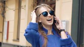 Gelukkige vrouw die op de mobiele telefoon op de straat spreekt stock video