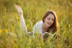 Gelukkige vrouw die op het gras liggen en een boek lezen stock foto's
