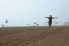Gelukkige vrouw die op het strand loopt Stock Foto