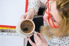 Gelukkige vrouw die op kantoor hete koffie drinken Royalty-vrije Stock Foto