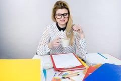 Gelukkige vrouw die op kantoor hete koffie drinken Stock Fotografie