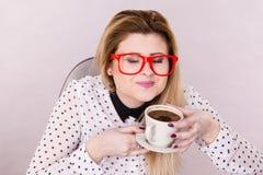 Gelukkige vrouw die op kantoor hete koffie drinken Stock Afbeeldingen