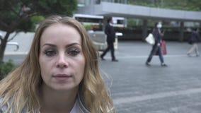 Gelukkige vrouw die op m-de achtergrond van de moderncitystraat aan camera kijken Gezichts mooie vrouw met sproeten die en glimla stock videobeelden