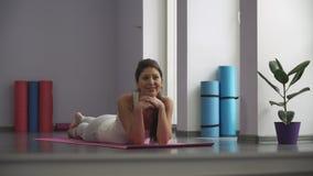 Gelukkige vrouw die op matte yoga liggen stock footage