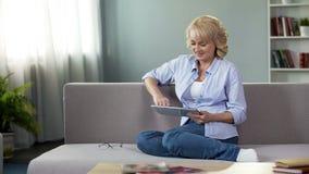 Gelukkige vrouw die op middelbare leeftijd grappige video's op tablet bekijken, die op laag thuis zitten stock foto's