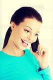 Gelukkige vrouw die op mobiele telefoon spreekt Stock Afbeelding