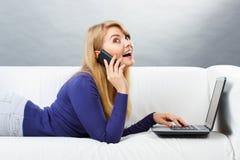 Gelukkige vrouw die op mobiele telefoon spreken en laptop met behulp van die op bank, moderne technologie liggen Stock Foto