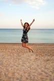Gelukkige vrouw die op strand springen. De zomervakantie. Stock Foto