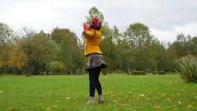 Gelukkige vrouw die in park in gele bladeren met paraplu dansen stock footage